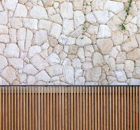 Courtyard cobble stone wall; honed teak rods on exterior ...
