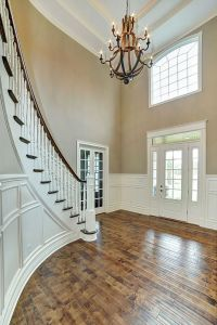 Curved staircase in two-story foyer with white wainscoting ...