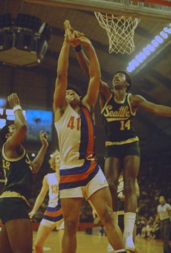 Wes Unseld of the Baltimore Bullets goes up and battles for a rebound with Joby Wright of the Seattle Supersonics during an NBA basketball game circa...: