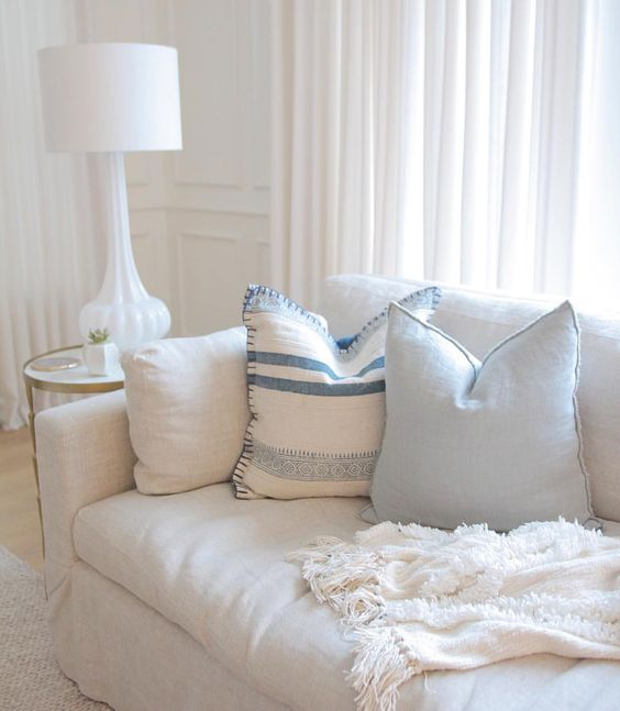 Coastal decor. Coastal blues. Coastal interiors. Lulu and Georgia Radde Pillow. Joss and Main grace pillow. horchow rippled glass lamp. one kings lane spike side table. anthropologie Aldalora throw blanket. Blue throw pillows. Restoration hardware sofa. Q design Centre drapery. Simply white Benjamin moore. Millwork. Coastal interiors. Hamptons Style. Braided Wool rug.: