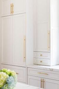 White cabinets adorned with long brass pulls and brass ...