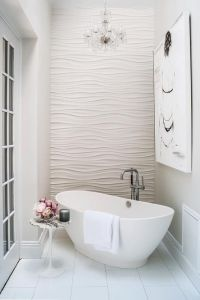 Romantic bathroom features an accent wall clad in wavy ...