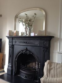 Beautiful iron fireplace with over mantle mirror above ...