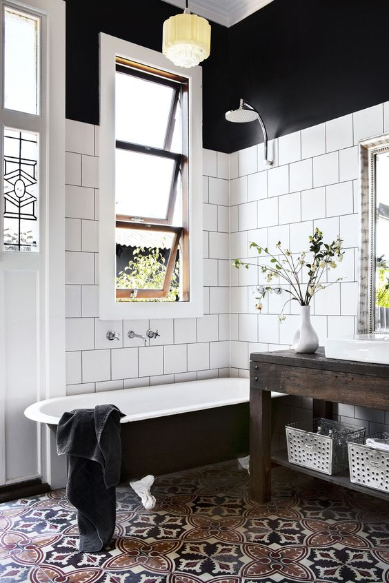 Small white and black bathroom with a patterned tile floor:
