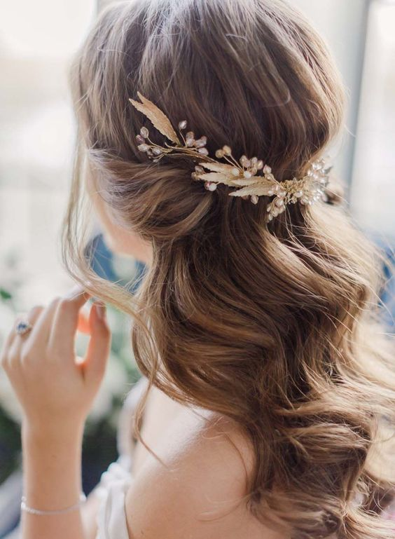 We're loving this romantic bridal hairstyle (especially the gorgeous gold hair accessory).: