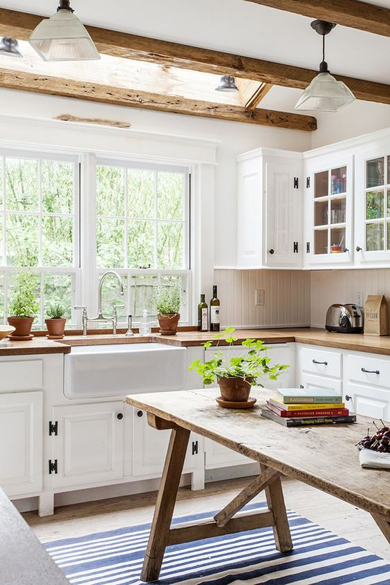 A stunning white and airy kitchen with beams in ceiling. Subway tiles, farmhouse sink, big bright window, this kitchen has it all!: