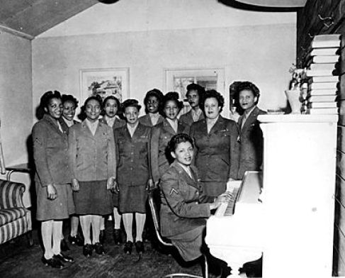 "Photo: Black Women's Army Corps personnel, in uniform, sit around a piano at Camp McCoy circa the 1940s. Women have served in the military at Fort McCoy since the World War II-era. Fort McCoy is celebrating ""A Century of Service"" during 2009. (History Center Photo):"