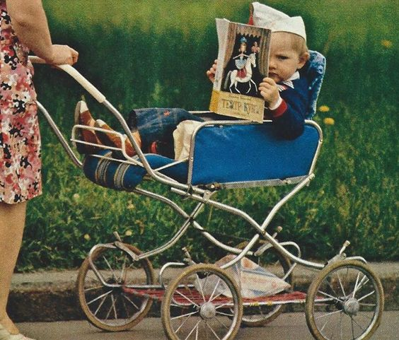 The delights of puppetry engross a tot in his stroller (Moscow, Russia) National Geographic | January 1978: