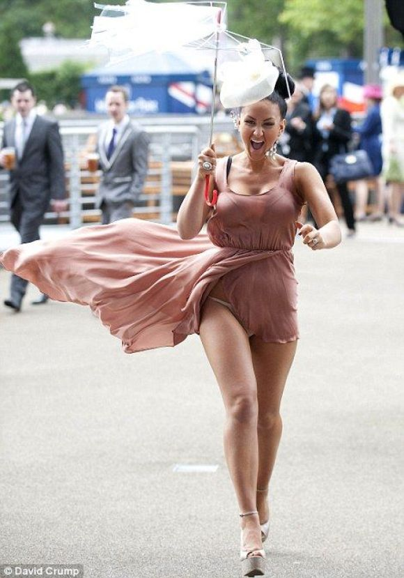Hold on to your hats (and your hemlines)! Ascot ladies battle with the wind as gales blowing through Royal course play havoc with race day outfits... Haha!!! Good ol' British weather... Part of the fun :):