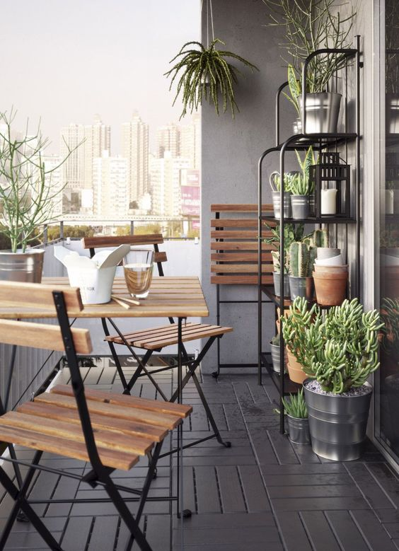 A small balcony furnished with a foldable table and three foldable chairs, all in solid acacia with black steel legs. Completed with a grey steel shelving unit filled with green plants in galvanised plant pots.: