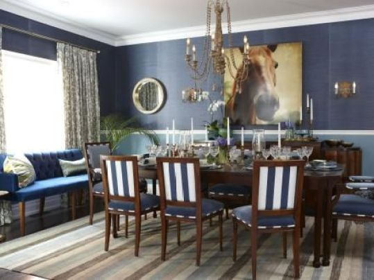 This dining room is a gathering space designed for fun. Blue grasscloth serves as a backdrop for graphic equestrian artwork, while a burst of turquoise beneath the chair rail adds unexpected boldness. Stripes on the rug and chair upholstery provide even more graphic punch.: