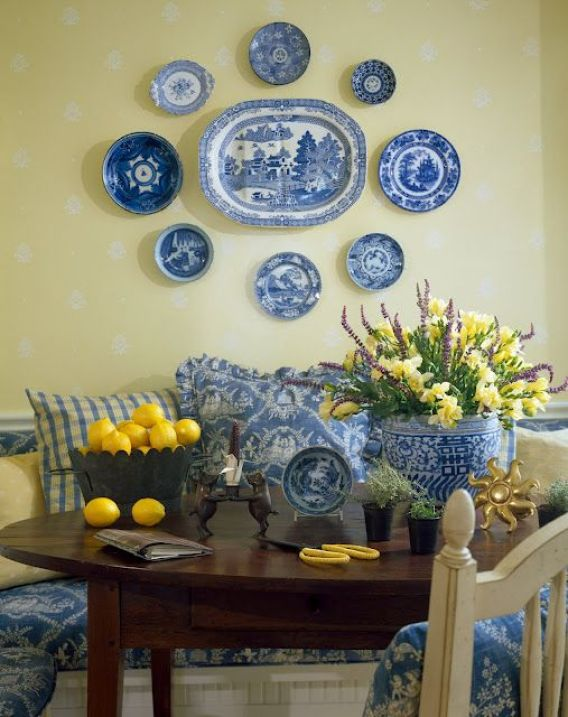 Wonderful arrangement of plates on a butter yellow wall. The lemon yellow accents work so well with the blue & white ~ what a cheerful breakfast room.: