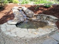 Rubble stone fountain leading into small man made pond ...