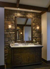 stone wall behind bathroom vanity, dark wood cabinet ...