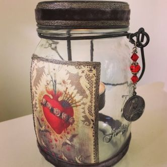 This rustic mason jar candle votive lantern features a vintage image of the Immaculate Heart of Mary. It is trimmed in gorgeous antique platinum ribbon from France. The lid and base of the lantern are