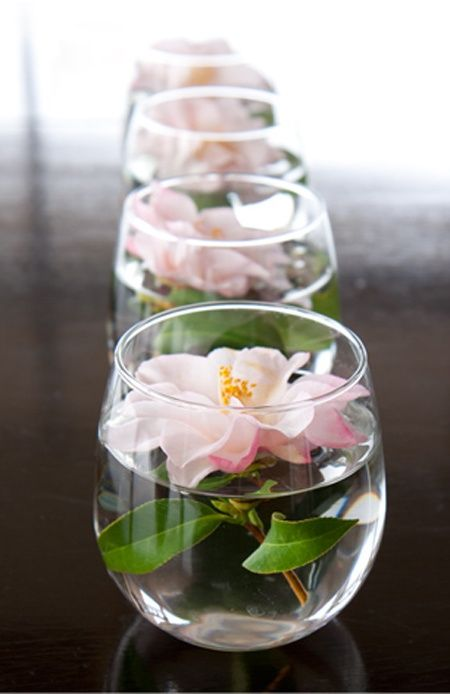 Small, short, and simple votives with flowers are great for decorating the bar, gift table and cake table at your wedding.: