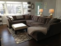 sectional couch with a sofa table behind and lamps for ...