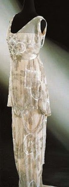 Evening dress, ca. 1913. Tunic-style double-layered front bodice and a skirt with a train. White net with embroidery of beads and pailettes.: