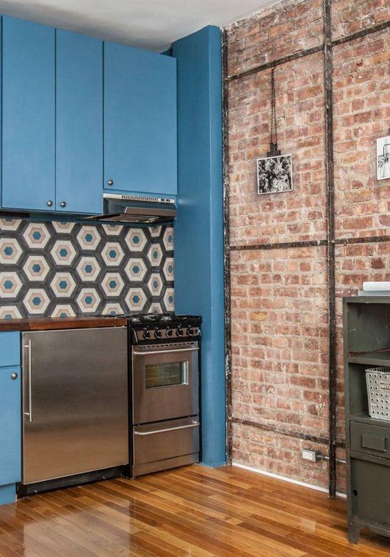 A cozinha, por exemplo, ganhou armários azuis que foram combinados à azulejos hexagonais cobertos de estampas geométricas.: