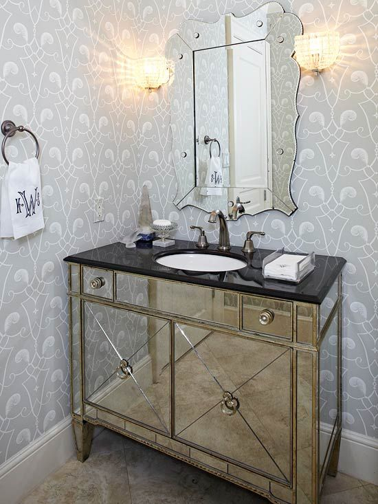 Beauty and Glam This stylish vanity cabinet makes the entire powder room sparkle with a hint of old Hollywood glamour. The mirror-paneled vintage chest was converted into a vanity, outfitted with vintage-style fixtures, and paired with an etched mirror to complete the dramatic statement.: