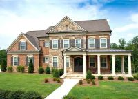 Six pillars define a wrap-around porch on this brick and ...