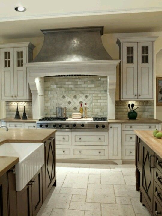 Two colored cabinets and travertine flooring.