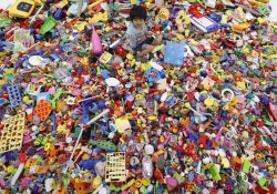 """A boy plays on an artwork made of unwanted toys at the solo exhibition of Japanese artist Hiroshi Fuji, known for his creations that recycle unwanted toys and waste materials, in Tokyo September 6, 2012. More than 100,000 unwanted toys collected by social groups across Japan for the past 13 years were used in the exhibition. Called """"Central Kaeru Station - where have all these toys come from?"""", the exhibition runs until Sunday. REUTERS/Kim Kyung-Hoon:"""
