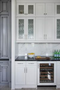 Chic kitchen bar boasts white cabinets fitted with leaded ...
