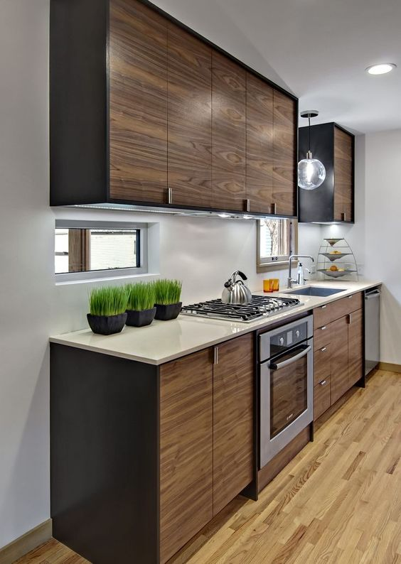 A modern galley kitchen layout with walnut cabinets
