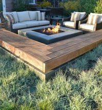 Fire pit surrounded by benches on a concrete slab ...