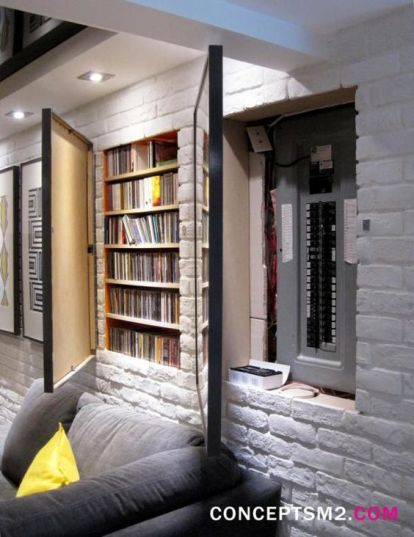 Hidden fuse box and media storage in wall hidden by hinged art frames for basement remodel by Concepts M2.:
