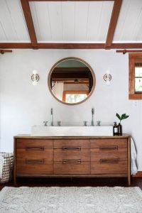 Bathroom with a mid-century sink vanity and round mirror ...