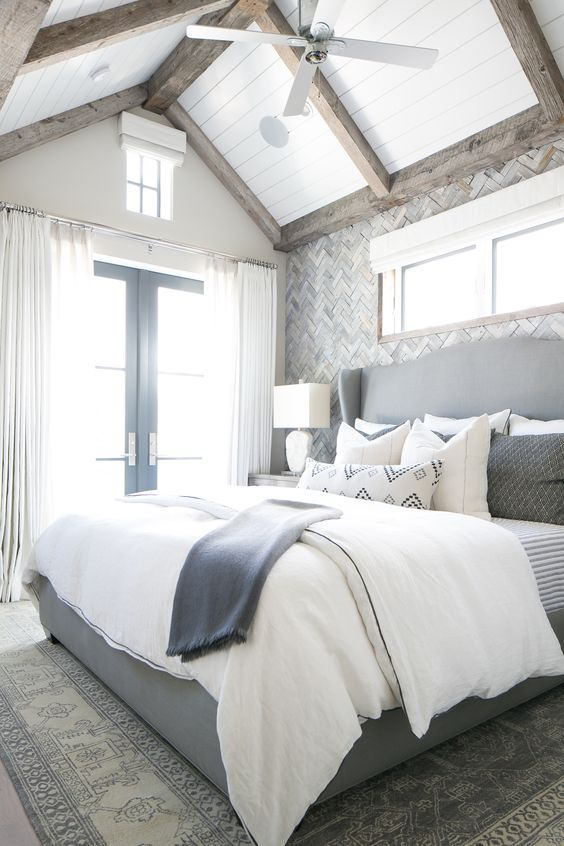 "Master bedroom in gray and white with ""shiplap"" ceiling, rustic beams, herringbone walls,:"