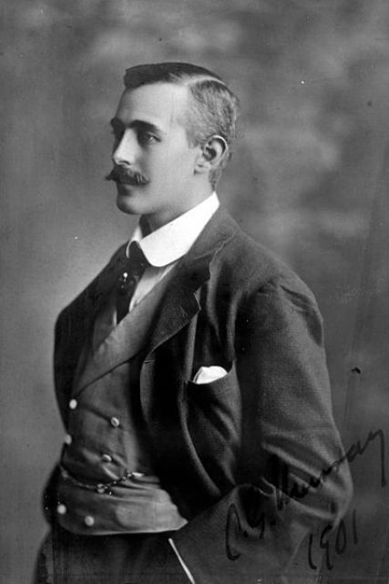A man pictured (1901) in a three-piece suit including a contrasting double-breasted waistcoat with a pocket watch: