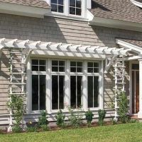 A shallow pergola and trellises give definition to this ...