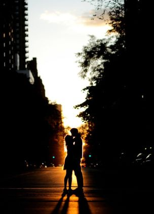 happy couple silhouetted in the late evening sunset - standing in the middle of the street - photo by New York City based wedding photographer Ryan Brenizer: