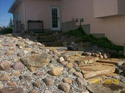 This Slope Of Natural Slab Steps And A Small Boulder Rock Garden