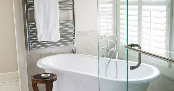 Free standing tub on an angle and glass corner shower with