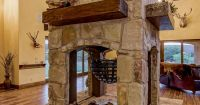 The wood-burning fireplace, with its four-sided design, is ...