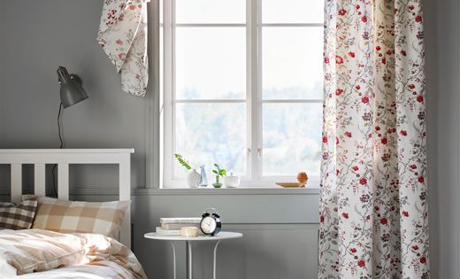 A Floral-printed Curtain Hangs In A Window In A Bedroom