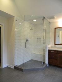 Gray tile flooring with subway tile shower walls and bench ...
