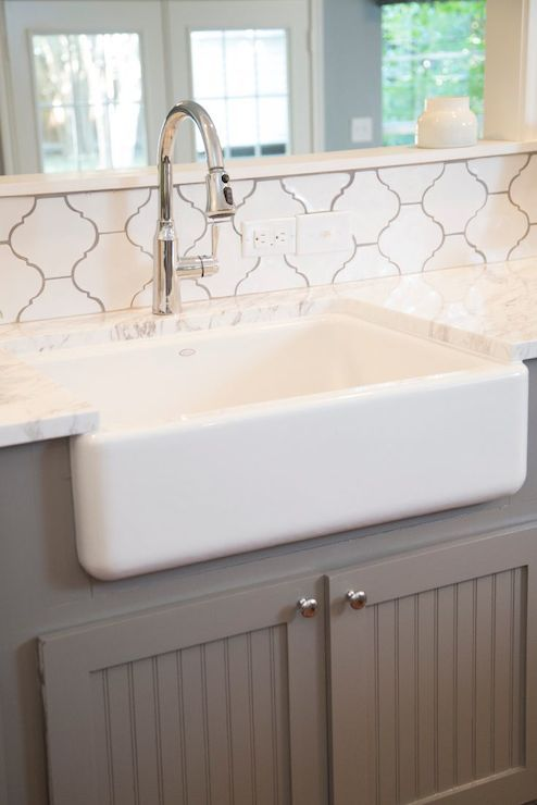 Fixer Upper - White and grey kitchen features pass through over gray beadboard, base cabinets framing farmhouse sink accented with gooseneck faucet paired with white quartz countertops and white arabesque tile backsplash, Home Depot Merola Tile Provenzale Lantern White.:
