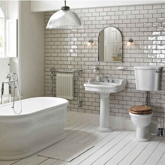 One of the most stunning bathrooms with a large bath tub, a basin with a full length pedestal and a close compact toilet with soft