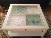 Sea glass & sand dollars displayed in a glass top coffee ...