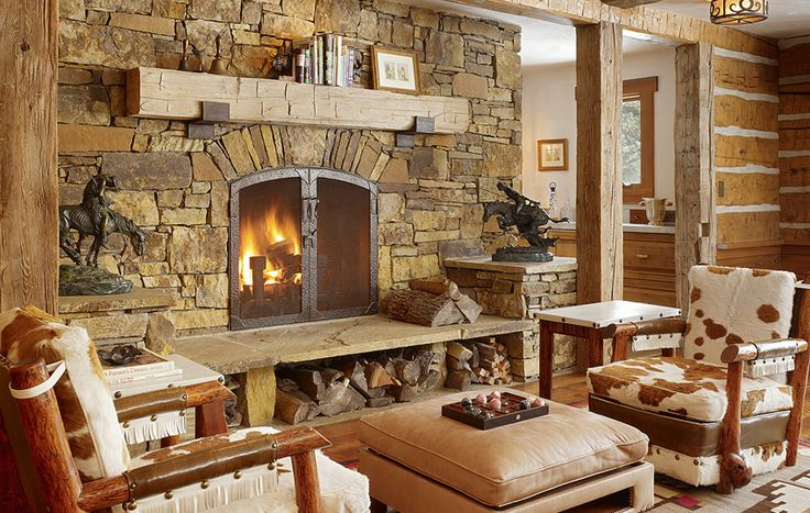Massive stone fireplacemassive rustic reclaimed wood mantel supported by steel corbels
