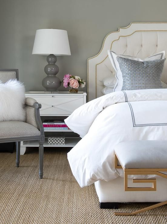 Tufted linen headboard with brass nailheads Gray lamp on