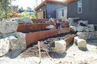 Incorporate boulders and metal retaining wall into garden