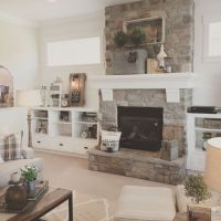 White plank walls surround this stone fireplace for a ...