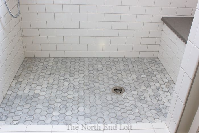 The shower floor is hexagonshaped marble tiles with