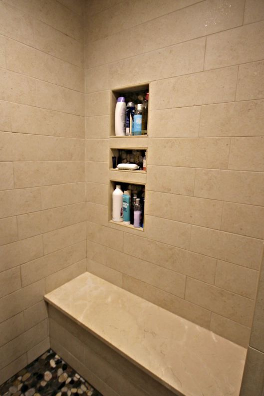 Custom Shower Niche with River Rock Details and Crema Marfil Marble Shower Bench  Master
